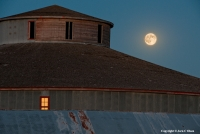 Round Barn Moon The last rays of the sunset illuminate a window on the Starke Round Barn as the full moon rises. This historic barn, located just north of Red Cloud, Nebraska was commissioned more than 100 years ago and was built without any nails or pegs, making it the only barn of its kind in the state.